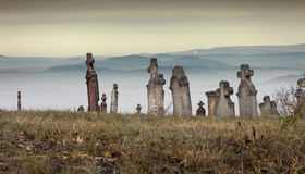 Toward the mountains. Old cemetery in front of the mountains on a cold, foggy day in Hungary Royalty Free Stock Images