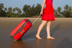 Towards adventure. The girl is rolling a red suitcase over the sandy surf belt. Royalty Free Stock Photography