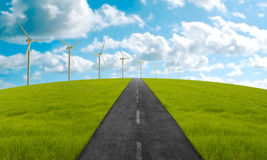 Towards the clean energy. Road in green meadow towards the clean energy system Stock Photos