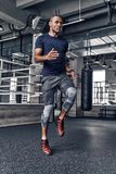 Towards the healthier lifestyle. Full length of handsome young A. Frican man in sport clothing jumping while exercising in the gym Royalty Free Stock Photography