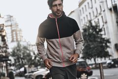 Towards a healthier lifestyle. Handsome young man in sport clothing looking away while running outdoors Royalty Free Stock Photos