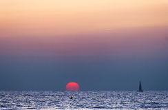 Towards the Sun. A sailboat is approaching the Sun at sunset on the coast of Rota, Spain Royalty Free Stock Image