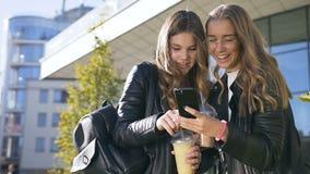 Towarzyskie caucasian dziewczyny używa przyrząd śmia się przy zabawa obrazkami na smartphone chodzi outdoors w parku zbiory wideo