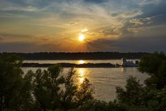 A towboat with barges in the Mississippi river at sunset near the city of Vicksburg in the State of Mississipp. I, USA stock image