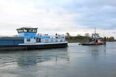 Towboat trekt stuurloos vrachtschip bij Nederlandse rivier Stock Afbeeldingen