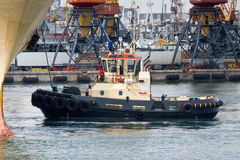 Towboat at work. Towboat pushing a big ship at the harbor Stock Images