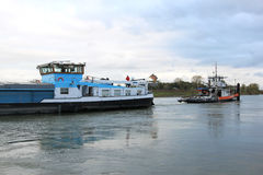 Towboaten drar den rudderless fraktbåten på den holländska floden Arkivbilder