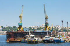 Towboats and cranes in shipyard Royalty Free Stock Image