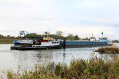 Towboats släpar den rudderless fraktbåten på den holländska floden Royaltyfria Bilder