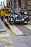 Towed motorcycles. Towing car removing motorcyles  because of parking violations in Florence, Italy .towing truck Royalty Free Stock Images
