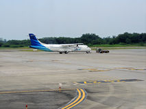 Towed turboprop aircraft. An ATR-72 turboprop aircraft being towed by tow truck in an airport in North Sumatera, Indonesia Stock Image