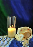 Relaxing and Rejuvenating Scene. Glowing yellow candle next to ceramic bowl spilling over with bath salts and soaps on a crip green and blue background Stock Photos