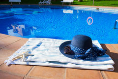 Towel and bathing accessories near pool Stock Photos