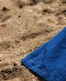 Towel on the beach. Blue towel on a sunny beach on a beautiful summer day Stock Images