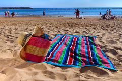 Towel and beach basket on sandy beach Royalty Free Stock Image