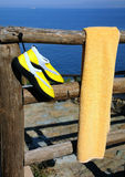 Towel and Beach Shoes on Wooden Fence. Yellow beach shoes and towel are drying on the wooden fence in the background of the sea Royalty Free Stock Photo