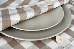 Towel in beige plaid and gray plates. Kitchen towel and plates. Royalty Free Stock Photos