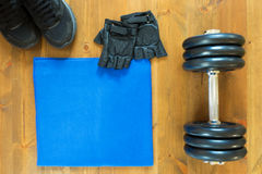 Towel with dumbbells for sports in the hall. Things to exercise lie on a board Royalty Free Stock Images