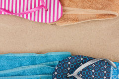 Towel and flip flops on the sand Stock Images