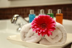 Towel and flower. With cosmetic in background Stock Photos