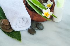 Towel, flowers, green leaves and cosmetics stock photography