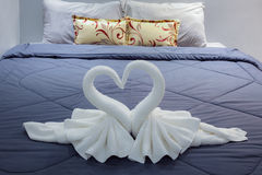Towel folded in swan shape on bed sheet Stock Images