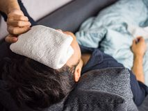 Towel on forehead, on man feels sick.  Royalty Free Stock Image
