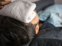 Towel on forehead, on man feels sick.  Royalty Free Stock Images
