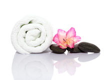 Towel, gladiola and pebbles for massage Royalty Free Stock Photo