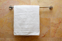 Towel on a hanger. Clean white towel on a hanger, marble Stock Photo