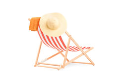 Towel and hat on a sun lounger with stripes Stock Photo