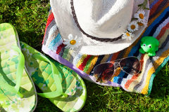 Towel, hat, sunglasses and chamomile on grass Royalty Free Stock Photos