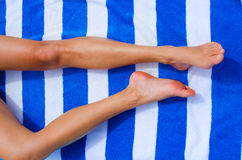 Towel legs. A pair of woman legs on a holiday towel Royalty Free Stock Images