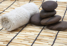 Towel and polished stone on bamboo Royalty Free Stock Images