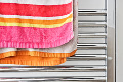Towel rail. Colorful towel hanging on a heated rail stock photos