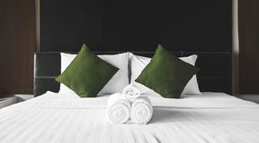 Towel rolls with green pillows on bed Stock Photography