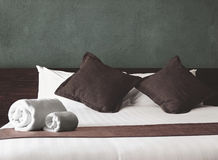 Towel rolls and pillows on bed Stock Photography