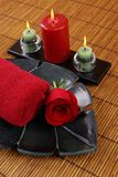 Towel and Rose. Towel, rose, and candles on bamboo mat Stock Photo