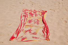 Towel on sand beach. Red towel covered by  sand on sandy beach. Perfect vacations Royalty Free Stock Image