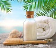 Towel with sea salt and seashells on beach table Royalty Free Stock Photography