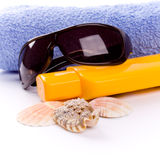 Towel, shells, sunglasses and lotion Stock Photos
