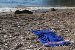 Towel on shingle beach Royalty Free Stock Photo
