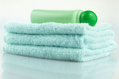 Towel and skin care products. A bottle of skin-care products and a towel together Royalty Free Stock Photography