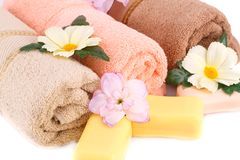Towel, soaps and flowers. Rolled towels, soaps and flowers closeup picture Stock Images