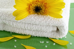 Towel spa white-green-yellow flower. White towel close up with yellow flower and bath salt on green background Stock Photo