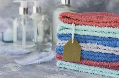 Towel stack with price tag on a white marble background, space for text, selective focus Royalty Free Stock Images