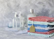 Towel stack with price tag on a white marble background, space for text, selective focus Stock Image