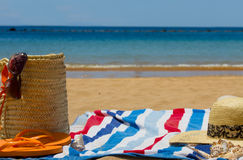 Towel and sunbathing accessories on  bech Royalty Free Stock Images