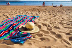 Towel and sunbathing accessories on sandy beach Stock Photos