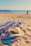 Towel and sunbathing accessories on sandy beach Stock Images